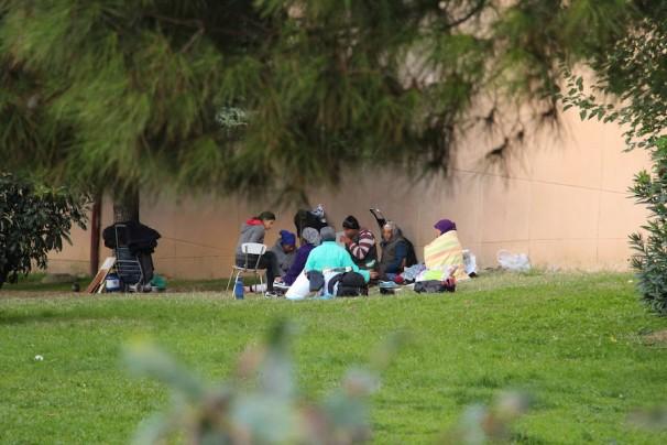 El grupo de gitanos comen juntos en el cesped de la vía que da acceso a la calle Virgen de la Paz. Fotos: M. Ruiz de Arcaute