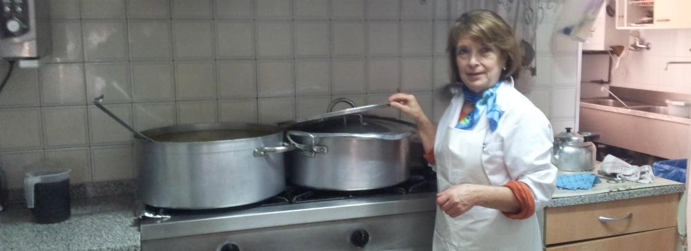 Isabel, una de las voluntarias del comedor, terminando el cocido con 21 kilos de pollo que será el plato del día. Fotos: U. M.