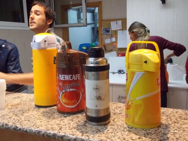 Cuatro termos con café. En la cocina faenan los voluntarios. Contra la miseria, caridad