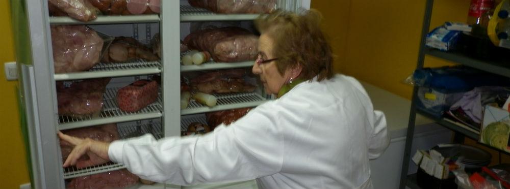 Una voluntaria muestra la nevera llena de carne