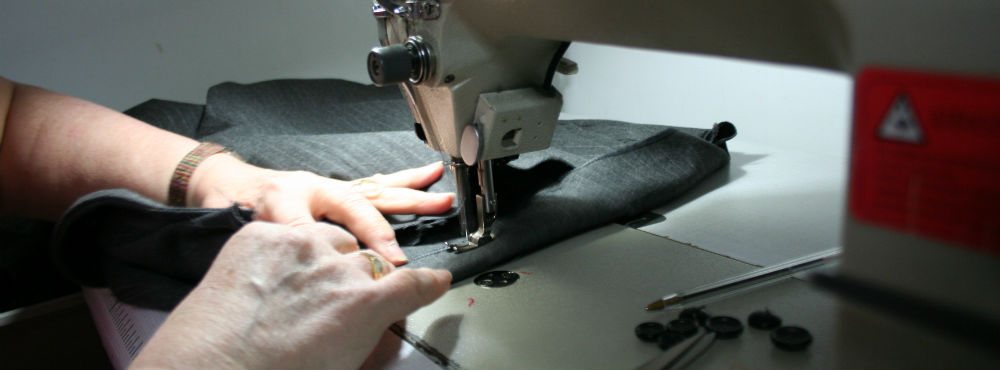 Unas manos cosiendo a máquina un bajo de un pantalón