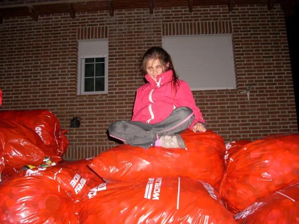 Lucía Gil sentada sobre una montaña de sacos llenos de tapones