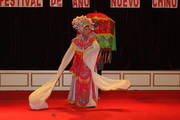 Una mujer asiática realiza un baile tradicional durante la fiesta