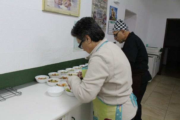 Los voluntarios Maite Galdón y José preparan el almuerzo. Fotos: M. Dorado