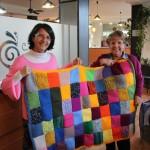 Concha y Marisol muestran una manta que las tejedoras han unido a partir de «cuadritos» de 10x10cm