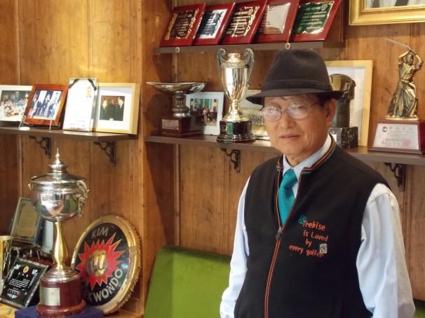 Kim Jae Won, superviviente de la guerra de Corea, posa junto a su vitrina