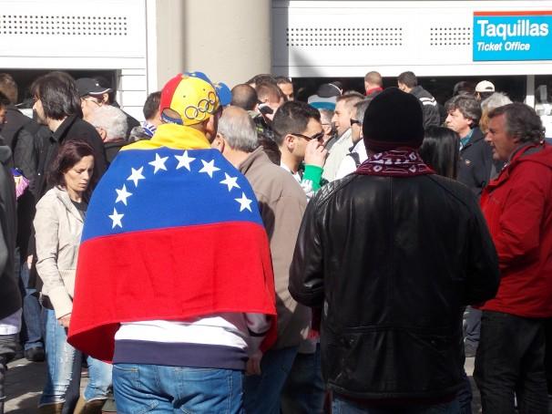 Dos madridistas venezolanos, uno envuelto en la bandera patria
