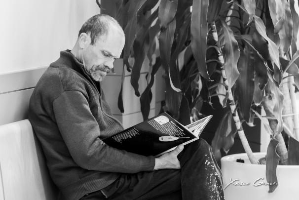 Miguel se sienta estos días en un banco del recibidor para leer. Foto: Xisco García