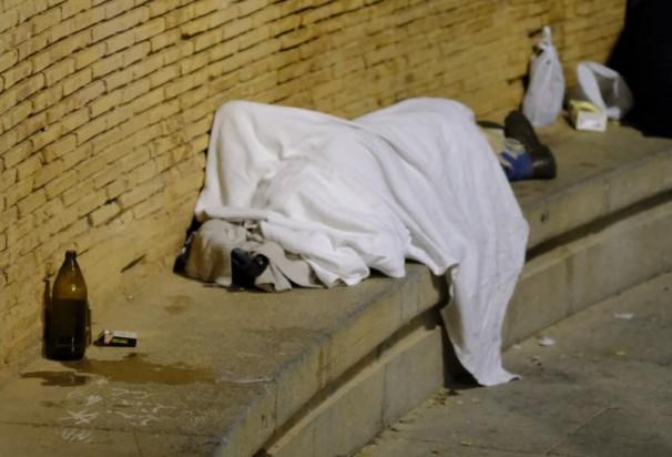 Una persona duerme en la plaza del 2 de Mayo junto a un litro de cerveza