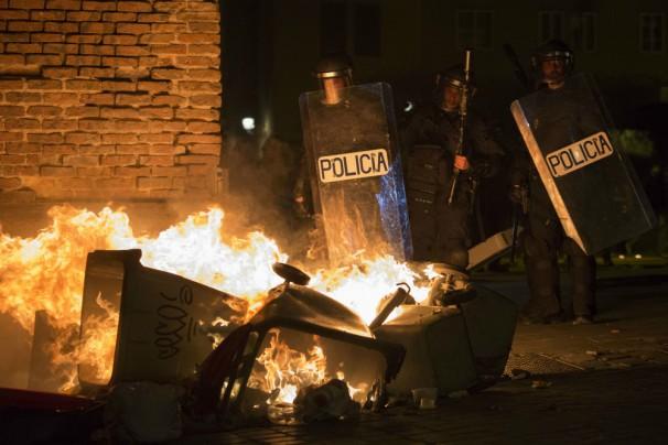 Cubos ardiendo frente a antidisturbios en Lavapiés. FOTO: AFP