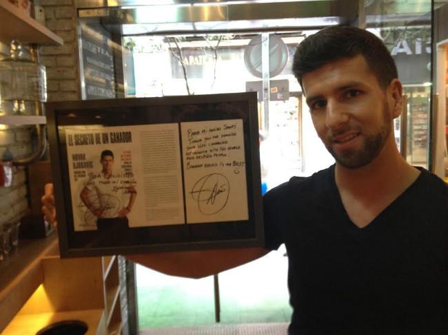 Santiago Godfrid, dueño de la pastelería Celicioso, posa con la fotografía de Novak Djokovic