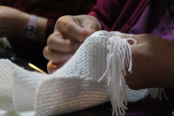 Una mujer cose una etiqueta a una bufanda
