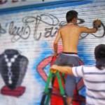 El graffitero David Jiménez pintando la persiana de un local