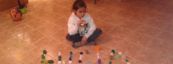 Lucia Gil posa junto a su nombre escrito con los tapones con los que financiará parte de su tratamiento en Philadelphia (EE.UU)