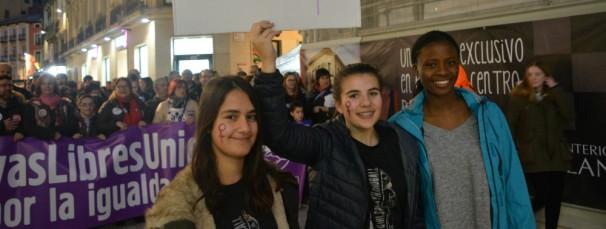 Tres jóvenes delante de una de las cabeceras de la manifestación del 8-M en Huesca - FOTO: G. C.