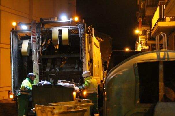 Los peones enganchan los contenedores al camión de carga trasera