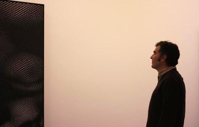 Alberto de Juan, galerista de Max Estrella, contempla una de las obras de Aitor Ortiz