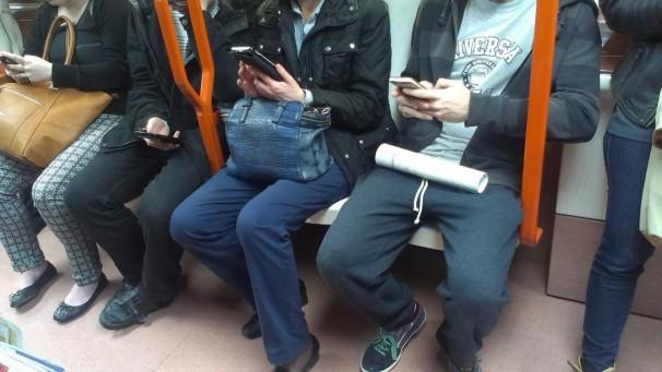 Personas miran su móvil en un andén del metro