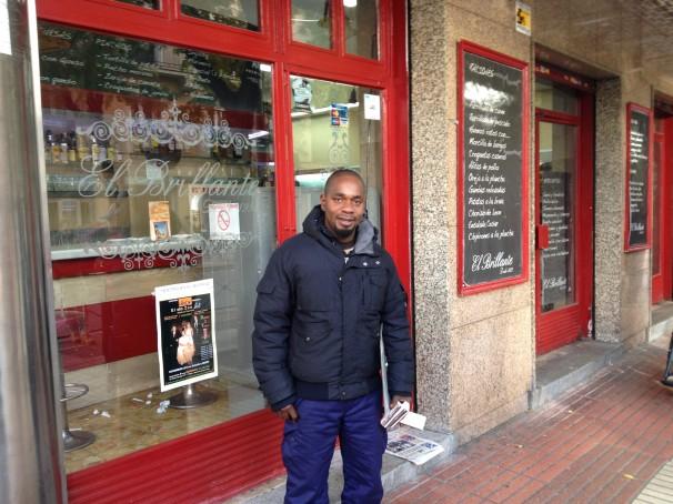 John Igbinosa en la puerta del bar donde «trabaja» cada día