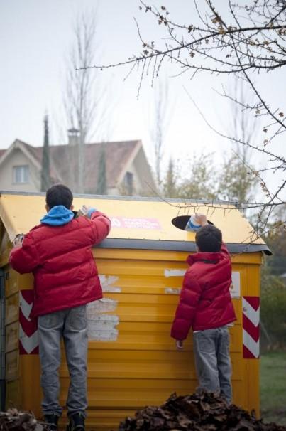 Dos niños reciclando sus envases de plástico en el contenedor amarillo/ ABC