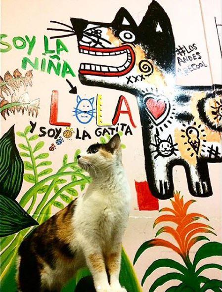 Lola posa delante de su mural