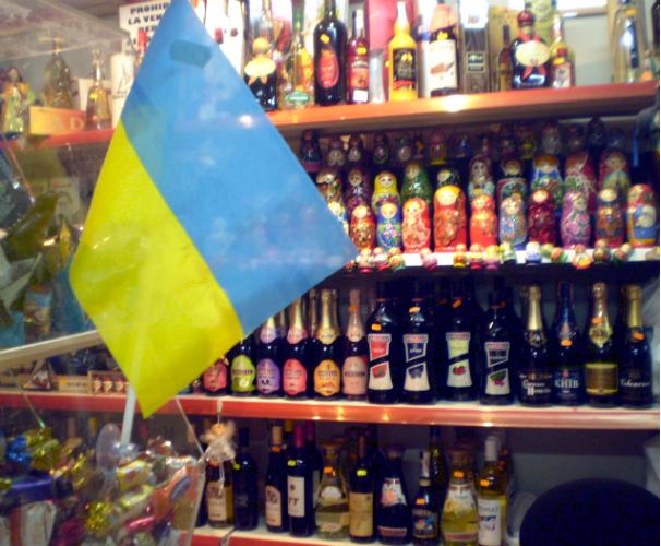 La bandera de Ucrania sobre un fondo formado de muñecas rusas, en una tienda de comida de Europa del este