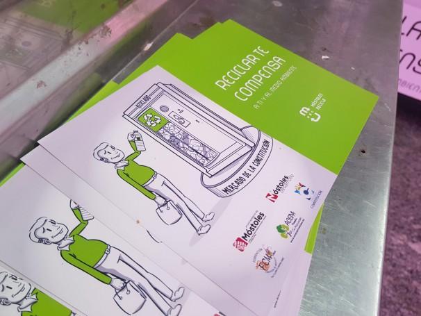 Panfleto informativo de la iniciativa apoyado sobre uno de los mostradores del Mercado de la Constitución