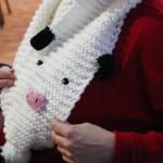 Una de las tejedoras voluntarias se prueba la bufanda-vaca